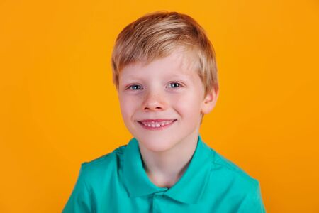 cute adorable schoolboy wearing turquoise t-shirt on yellow background