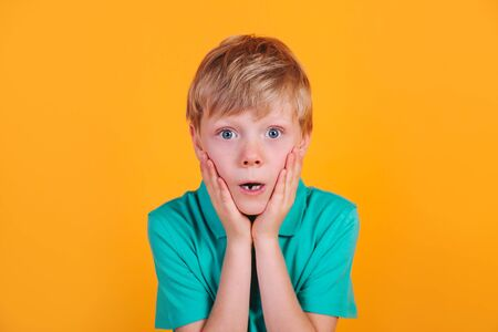 Photo of shocked little boy child with freckles over yellow background. Looking camera. 免版税图像