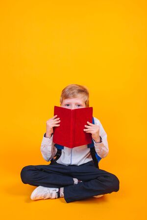 7 year old school boy sitting reading with backpacks on yellow background