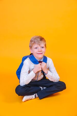 Little school boy with backpack sitting over orange background