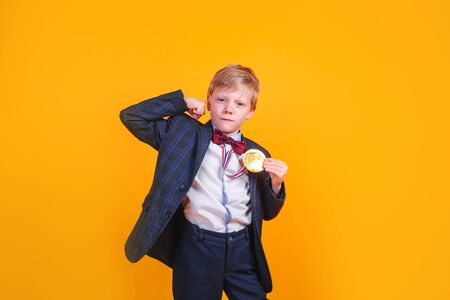 Pretty small boy in black suit with gold medal on his neck over yellow background