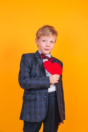 Charming little boy posing with heart on yellow background 免版税图像