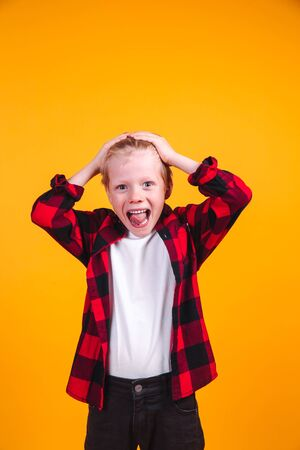 Terrified blond hair boy clutched at his head on yellow background