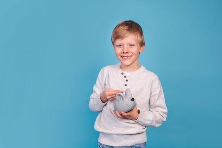 portrait of cute little boy putting money in moneybox 免版税图像
