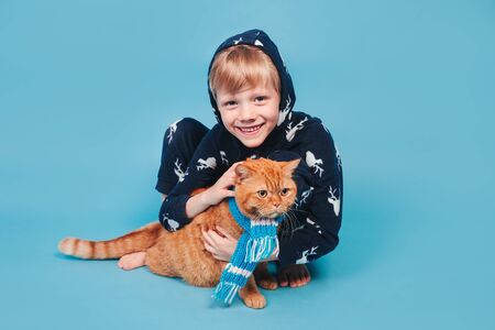 Kid in soft warm pajamas playing with red cat on yellow background