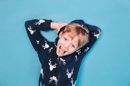 Funny cute boy in pajamas lying on blue background 免版税图像