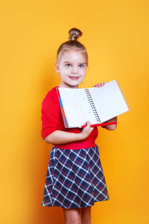 Smiling little student girl with notebook. Education and school concept .