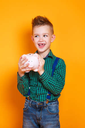 Little boy holding a piggy bank in his hands on yellow background