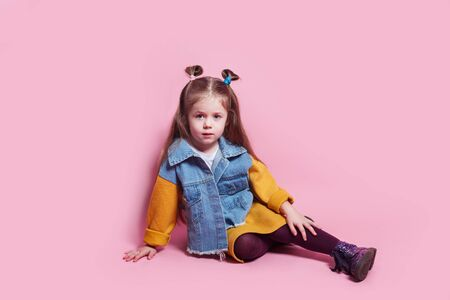 Stylish baby girl 4-5 year old wearing denim clothes posing on pink background