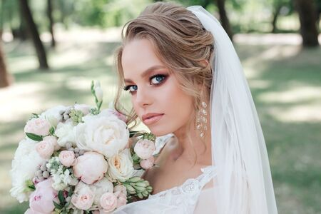 Beautiful bride with wedding flowers bouque in park. Bride with wedding makeup and hairstyle.