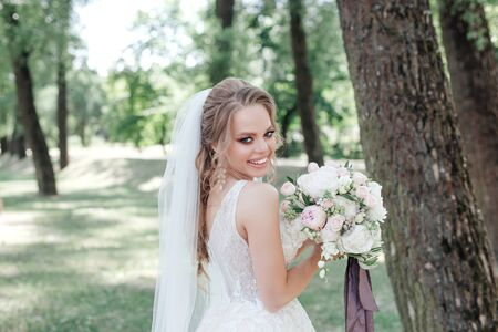 Beautiful bride with bouquet smiling outdoor in park 免版税图像