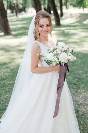 Stunning young bride holding wedding bouquet and smiling at camera outdoor