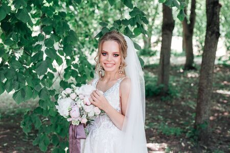 Beautiful young bride holding wedding bouquet and smiling at camera outdoor