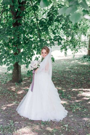 Amazing bride in beautiful white wedding dress hold bouquet of flowers in her hands.