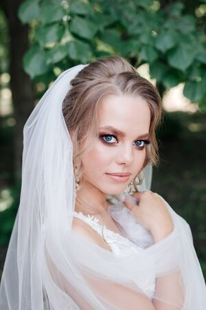 Glamorous young bride in wedding dress outdoor
