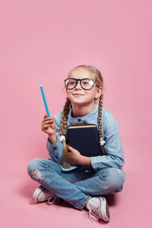 Schoolgirl in glasses pointing pencil at empty space for text