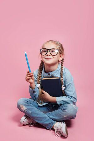 Schulmädchen in Gläsern, die mit Bleistift auf leeren Raum für Text zeigen
