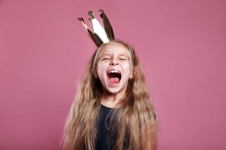 Shouting little girl in crown on pink background