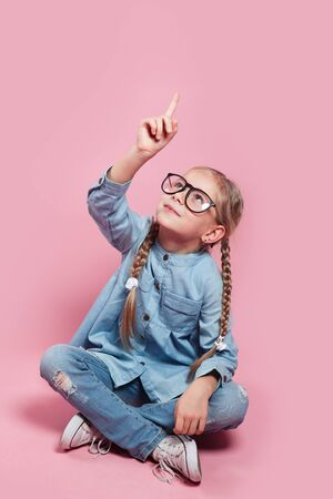 child with glasses points finger up on pink background