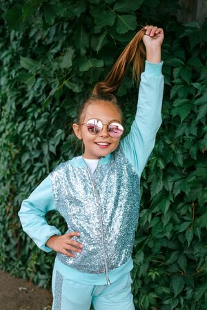 Stylish little girl child wearing a summer or autumn clothes, sunglasses outdoor in park Banco de Imagens