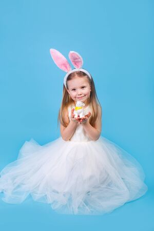 Cute positive little girl wearing bunny ears holding easter rabbit on blue studio background. Happy Easter