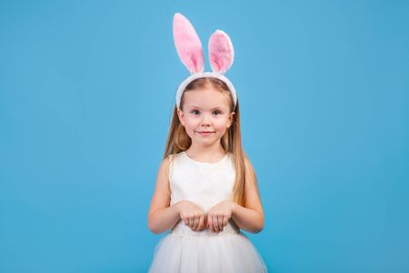 Cute little child girl is wearing bunny ears on blue background. Happy easter