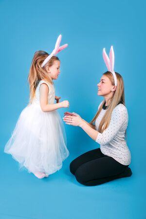 Mother and daughter in bunny ears headbands having fun on blue background