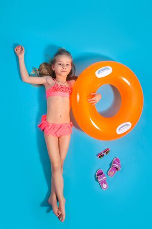 Top view of a little girl lying on the floor with slippers and a inflatable circle on blue background