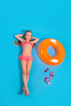 Top view of a little girl lying on the floor with slippers and a inflatable circle on blue studio background
