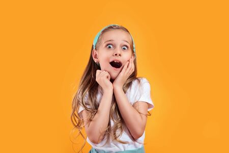 Little girl screams into the camera, folded his palms at his mouth on yellow background