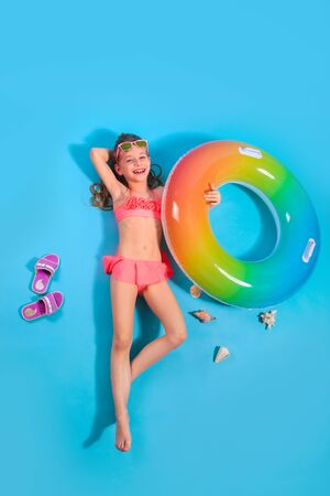 Happy child girl in swimsuit lying with swimming ring on blue background