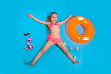 Niña bonita se relaja con círculo inflable sobre fondo azul. Concepto de viajes de verano.