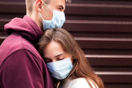 Young couple hugging wearing a face protection mask in the city since new coronavirus Covid 19
