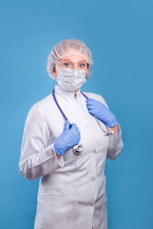 Portrait of female doctor in special surgical sterile protective clothing on blue studio background