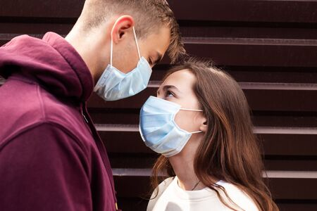 Young loving couple wearing face masks, hugging and looking at each other eyes outdoor