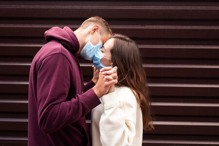 Couple in quarantine trying to kiss wearing a mask outdoor . Focus on hands Foto de archivo