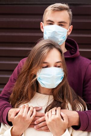 Quarantine romantic. Young couple hugging each other with protective medical masks outdoor