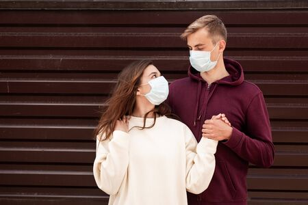 Young couple with face masks in time of virus pandemic in city
