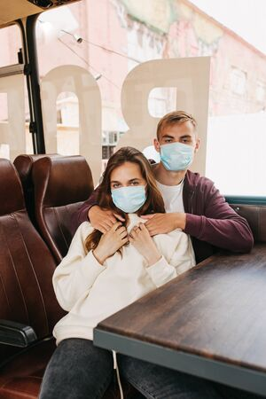 Young couple in bus, travelling together, wearing hygienic mask to prevent the virus