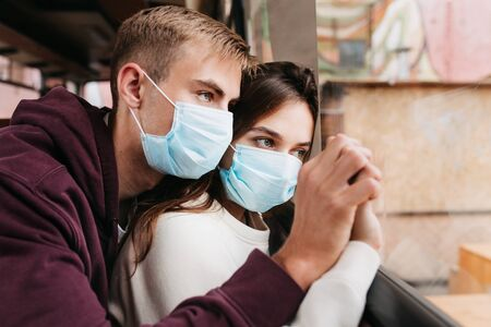 Young sad couple in protective masks at home in quarantine covid-19