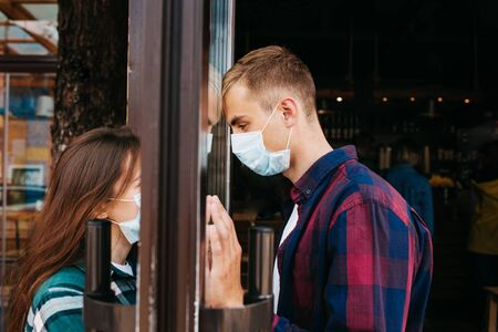 Man in medical protective face mask looking through window on her girl .Coronavirus pandemic covid-19.