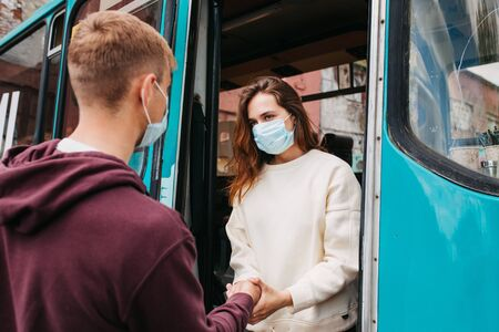 Coronavirus, covid 2019, young couple with respiratory masks traveling in the public transport by bus
