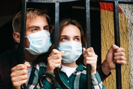 Self-isolation in pandemic. Couple in protective masks on quarantine. Covid-19