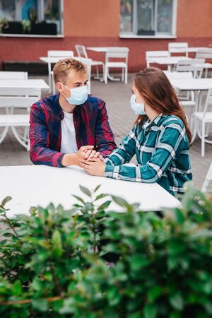 Cute couple wearing protective medical masks sitting at table and talking in street cafe.