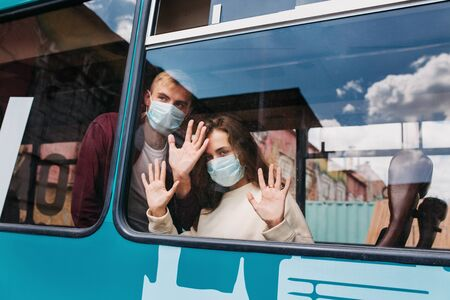 covid 2019, young couple with respiratory masks traveling in the public transport by bus