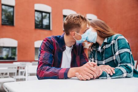 Couple in love, man and woman kissing each other in protective medical mask on face in city Foto de archivo
