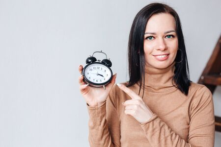 Close-up portrait of beautiful girl looking at you and holding an alarm clock in her hand, Time-management