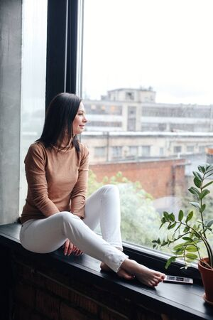 Young relaxing woman looking through the window with a city view, sitting on a windowsill