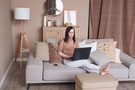 Relaxed woman on sofa with laptop working at home Foto de archivo