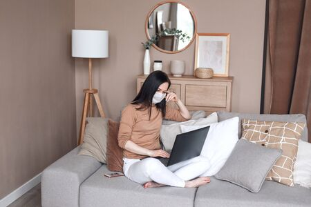 Woman in quarantine for coronavirus wearing protective mask and smart working on sofa at home office